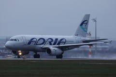 Plano de Adria Airways que taxiing na pista de decolagem imagem de stock