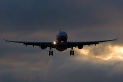 Plano de Airbus A330 que aterra o por do sol perfeito do céu Imagem de Stock
