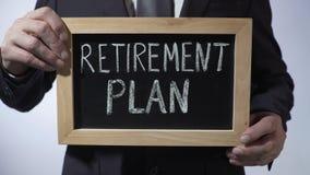 Plano de aposentação redigido no quadro-negro, homem de negócios que guarda o sinal, economias do dinheiro video estoque