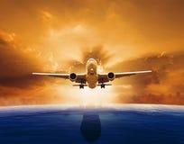 Plano de avião de passagem que voa sobre o nível do mar bonito com grupo do sol fotografia de stock royalty free