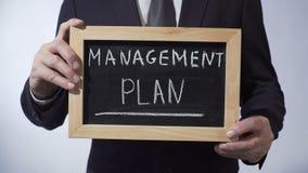 Plano de gestão redigido no quadro-negro, pessoa do negócio que guarda o sinal, estratégia filme