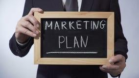 Plano de marketing redigido no quadro-negro, homem no terno preto que guarda o sinal, negócio vídeos de arquivo