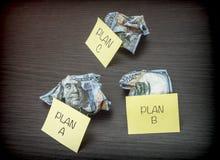 Plano de negócios falhado A, B e C, cédulas minted do dólar em uma mesa de madeira fotografia de stock royalty free