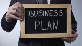 Plano de negócios redigido no quadro-negro, mãos masculinas que guardam o sinal, estratégia, objetivos vídeos de arquivo