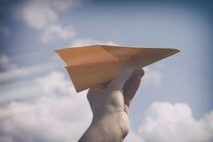Plano de papel em uma mão contra o céu nebuloso imagem de stock