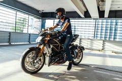Plano distante da motocicleta da equitação do motociclista no estacionamento Fundo urbano fotos de stock royalty free