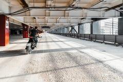 Plano distante da motocicleta da equitação do motociclista no estacionamento Fundo urbano fotografia de stock royalty free
