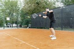 Plano distante do homem que joga o tênis na corte e que bate a bola com uma raquete imagens de stock