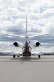 Plano do learjet dos aviões na frente do aeroporto com céu nebuloso Fotografia de Stock Royalty Free