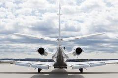 Plano do learjet dos aviões na frente do aeroporto com céu nebuloso Fotografia de Stock