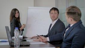 Plano do projeto de Presents A do gerente superior da mulher aos colegas em uma reunião no escritório video estoque