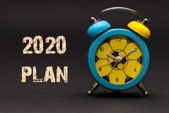 plano 2020 escrito com o despertador no fundo de papel preto Foto de Stock Royalty Free