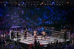 Plano geral da arena esportiva durante a luta no anel, nos lutadores e no árbitro através dos fãs do anel Foto de Stock