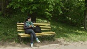 Plano geral de um banco de parque e da mulher com vidros em sua cabeça que senta e que usa o telefone celular video estoque