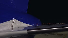 Plano no aeroporto da noite que espera a decolagem, curso com baixo custo, jato privado filme