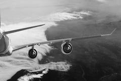 Plano no branco do preto do fundo do avião do transporte do curso do voo do céu fotografia de stock