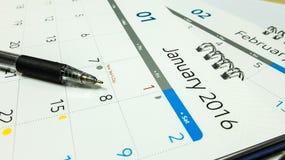 Plano pelo ano novo 2016, calendário de 2016 com pena e caderno na mesa de escritório Imagens de Stock
