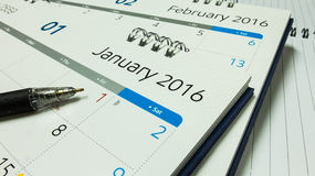 Plano pelo ano novo 2016, calendário de 2016 com pena e caderno na mesa de escritório Imagens de Stock Royalty Free