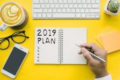 2019 plano, texto da lista de verificação no bloco de notas com homem de negócios e escritório foto de stock