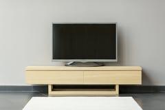 Plano-TV que se coloca en la cómoda en el cuarto imagen de archivo