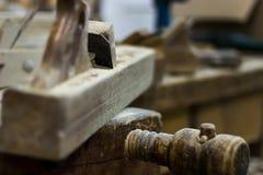 Plano velho em uma plaina de madeira do banco de trabalho do carpinteiro, plano da mão fotos de stock royalty free