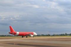Plano vermelho na pista de decolagem Fotos de Stock