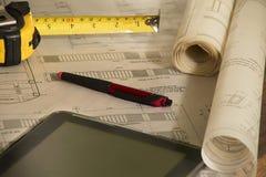 Planos arquitetónicos ao lado da pena, do medidor e do computador imagens de stock