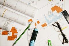 Planos da construção com as ferramentas do capacete e de desenho fotos de stock royalty free