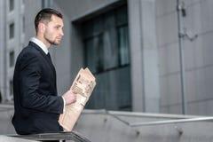 Planos financeiros contemplativos Homem de negócios que olham dianteiro e holdi Fotografia de Stock Royalty Free
