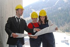 Plans. Boss holding construction plans and talking with workers Royalty Free Stock Image