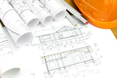 Plans of house with helmet and wooden ruler Royalty Free Stock Image