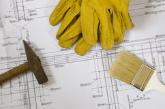 Plans and tools. Building plans with hammer, paint brush and working gloves on top stock photo