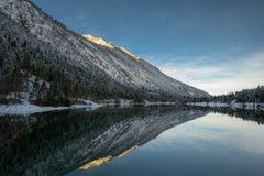 Plansee de lac au lever de soleil d'hiver avec refléter la montagne alpine image libre de droits