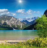 Plansee summer sunshiny landscape Austria. Plansee summer  sunshiny landscape with snow on mountainside, deep blue sky with cumulus clouds and sunshine, and Stock Image