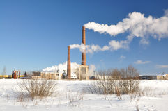 Plant. Smoke from two factory chimneys. Winter royalty free stock photo
