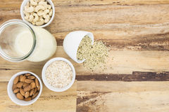 Plant based milk and and bowls with ingredients. On wooden background Stock Images