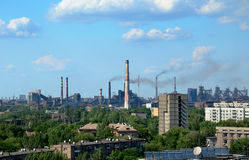 Plant in the city. Smoke from the chimneys polluting on blue sky background. horizontal Stock Images