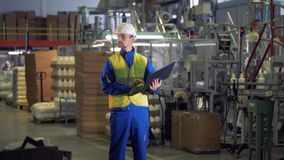Plant employee with a laptop is standing in the middle of a producing unit stock video footage