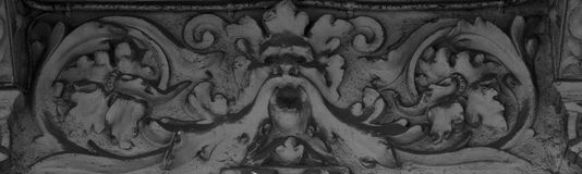 Plant face character screaming. Shot and black and white, detail on the sculpture on the facade of this historic building representing some plants / flowers / Royalty Free Stock Images
