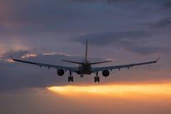 Plant flyg in mot landningsbanan under en molnig soluppgång Arkivfoto