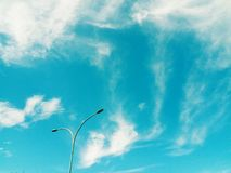 Street lamp pole under the sun light with beautiful sky and clouds in the background. Plant green red leaves beautiful sky clouds background stock image