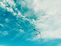 Street lamp pole under the sun light with beautiful sky and clouds in the background. Plant green red leaves beautiful sky clouds background royalty free stock image