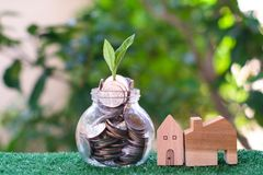 Plant growing from coins in glass jar. Wooden house model on artificial grass. Home mortgage and property investment concept. Copy space royalty free stock image