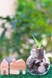 Plant growing from coins in glass jar. Wooden house model on artificial grass. Home mortgage and property investment concept. Copy space insurance door real royalty free stock photography