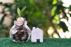 Plant growing from coins in glass jar. Wooden house model on artificial grass. Home mortgage and property investment concept. Copy space insurance door real stock photos