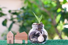 Plant growing from coins in glass jar. Wooden house model on artificial grass. Home mortgage and property investment concept. Copy space stock photography
