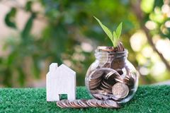 Plant growing from coins in glass jar. Wooden house model on artificial grass. Home mortgage and property investment concept. Copy space stock image