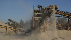 At the plant at high conveyor moves the sand and drops down. stock video footage