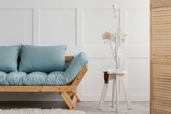 Plant and lamp on white stool next to blue wooden sofa in minimal living room interior. Real photo royalty free stock photos