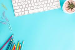 Plant lekmanna- foto av kontorsskrivbordet med blyertspennan och tangentbordet, workpace för bästa sikt på blå bakgrund och kopie arkivbilder